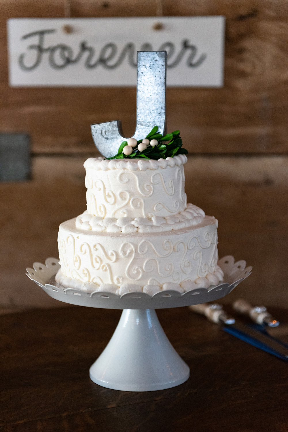Rustic two tier white wedding cake with couple's initial at Lewis Family Farms