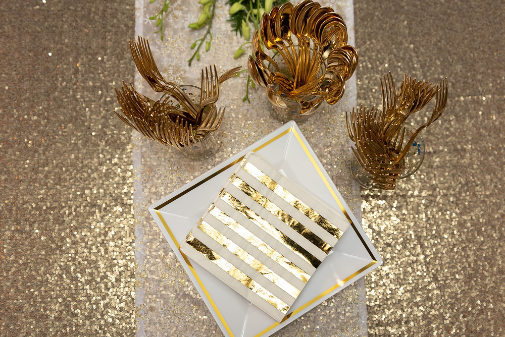 Gold sequin table cloth with gold forks and spoons and gold striped napkins