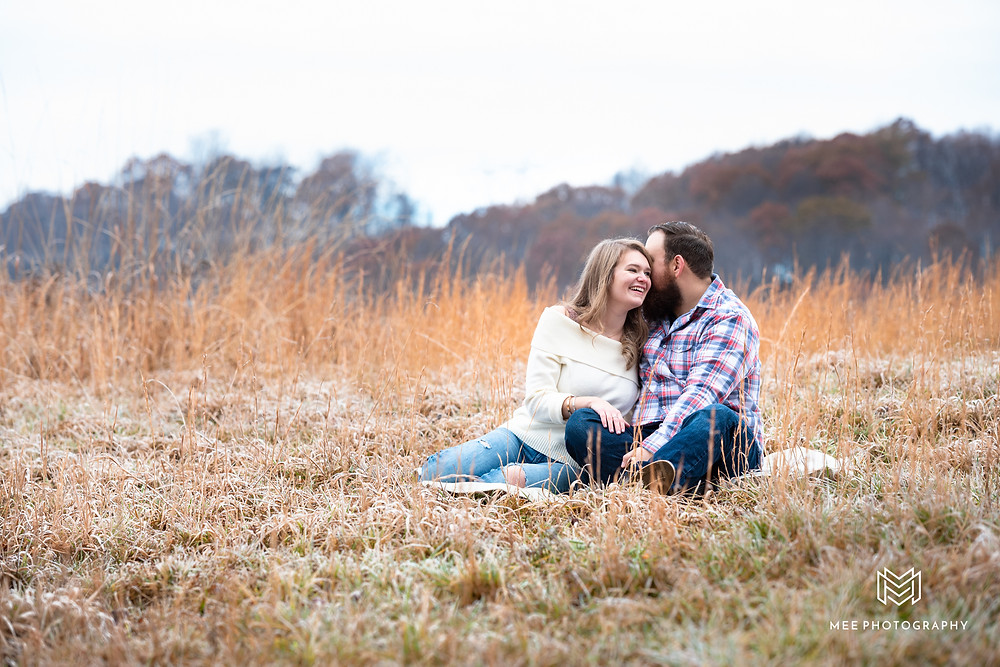 Couple sitting in a field during their Christmas photoshoot