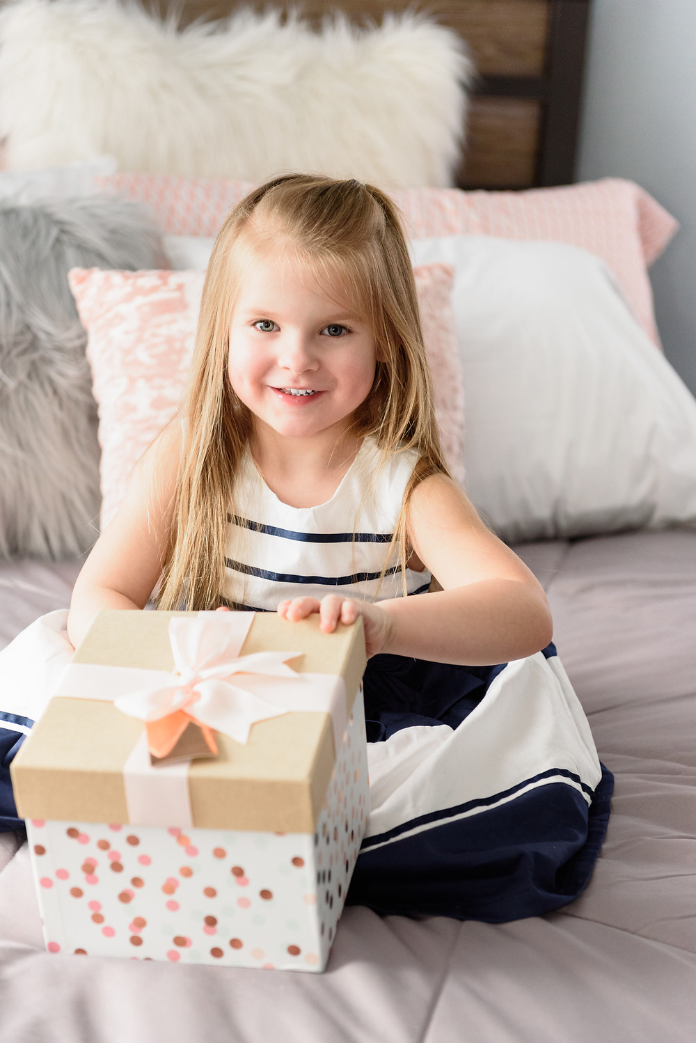 Young girl opening a presentin a pink and white gift box with a pink bow.