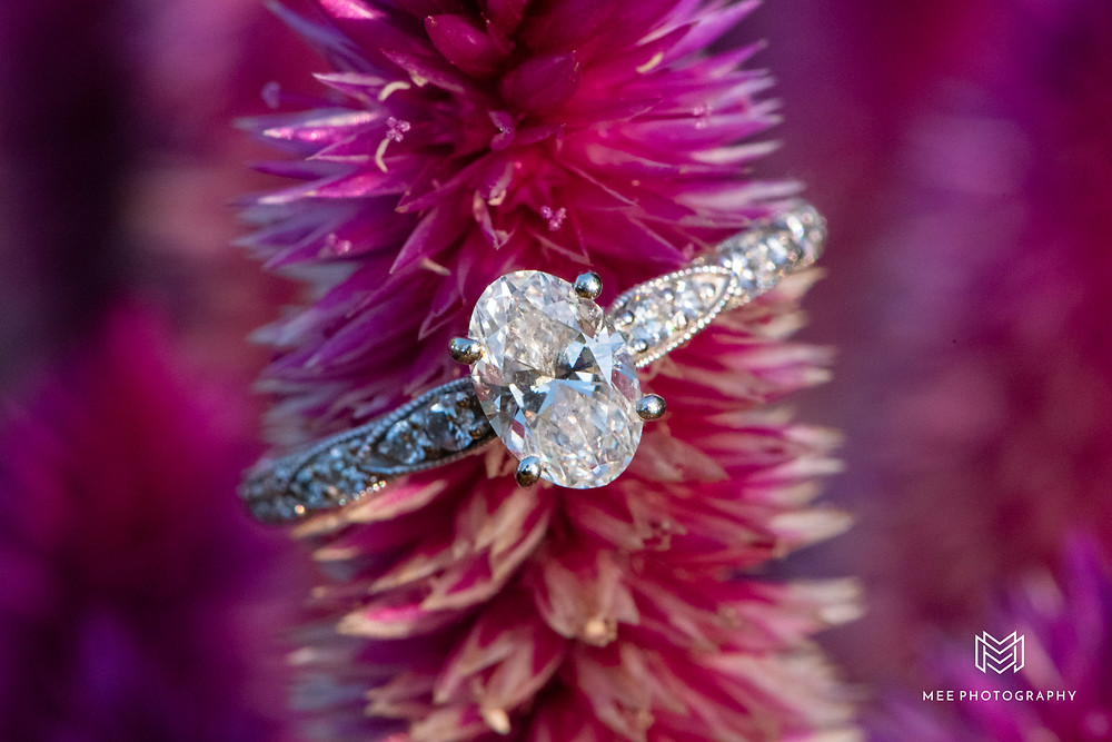 Oval diamond engagement ring positioned on pink flower