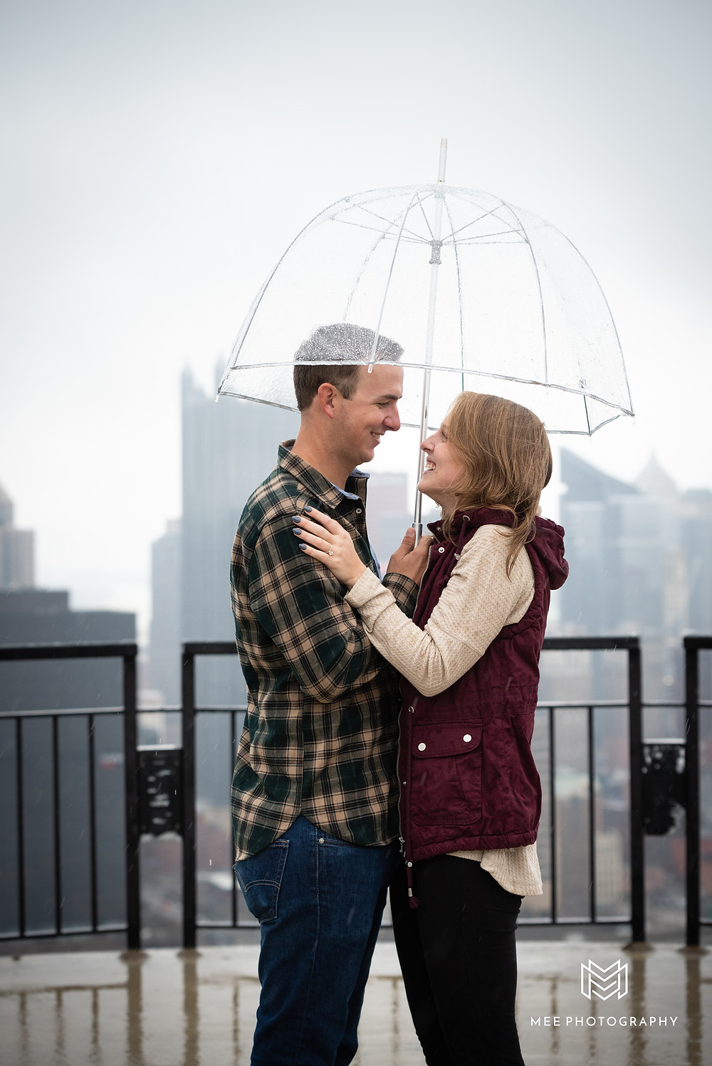 Newly engaged couple laughing under a clear umbrella in the rain on the Mount Washington Overlook