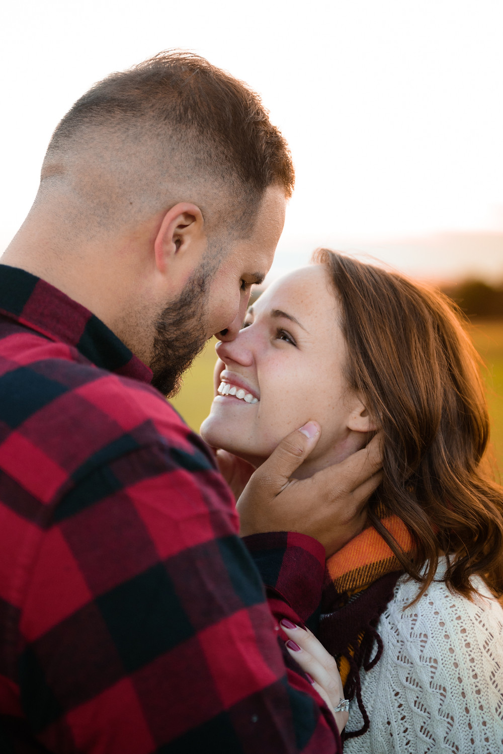 A cute couple laughing in plaid shirts during their country engagement shoot.