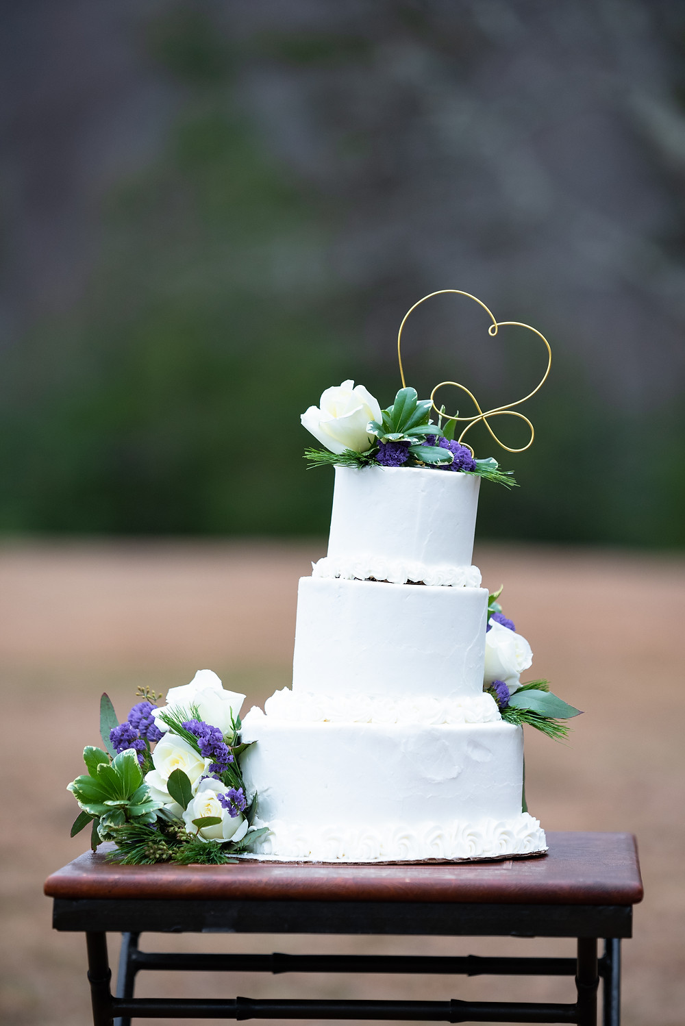 Three tiered wedding cake with white roses and metal heart on top