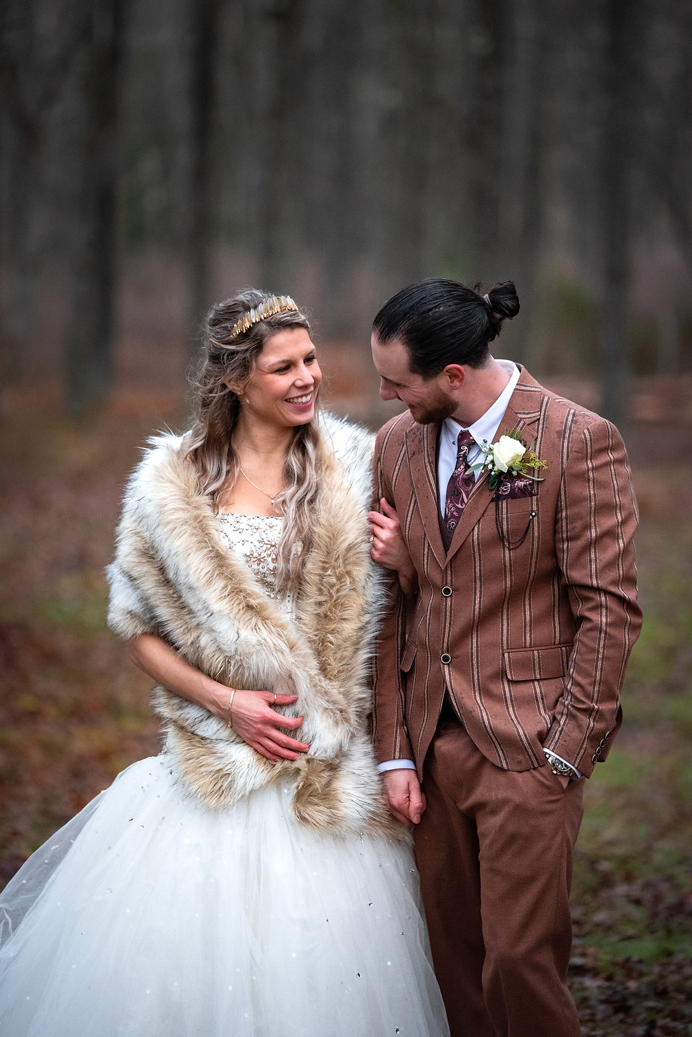 Bride and groom walking and laughing in the woods during their winter wedding