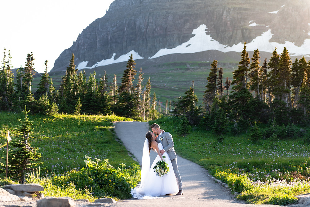 Bride and groom kissing with mountains in the background in Montana