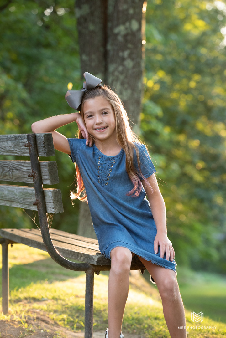 Child portrait of young girl in blue denim dress sitting on a park bench