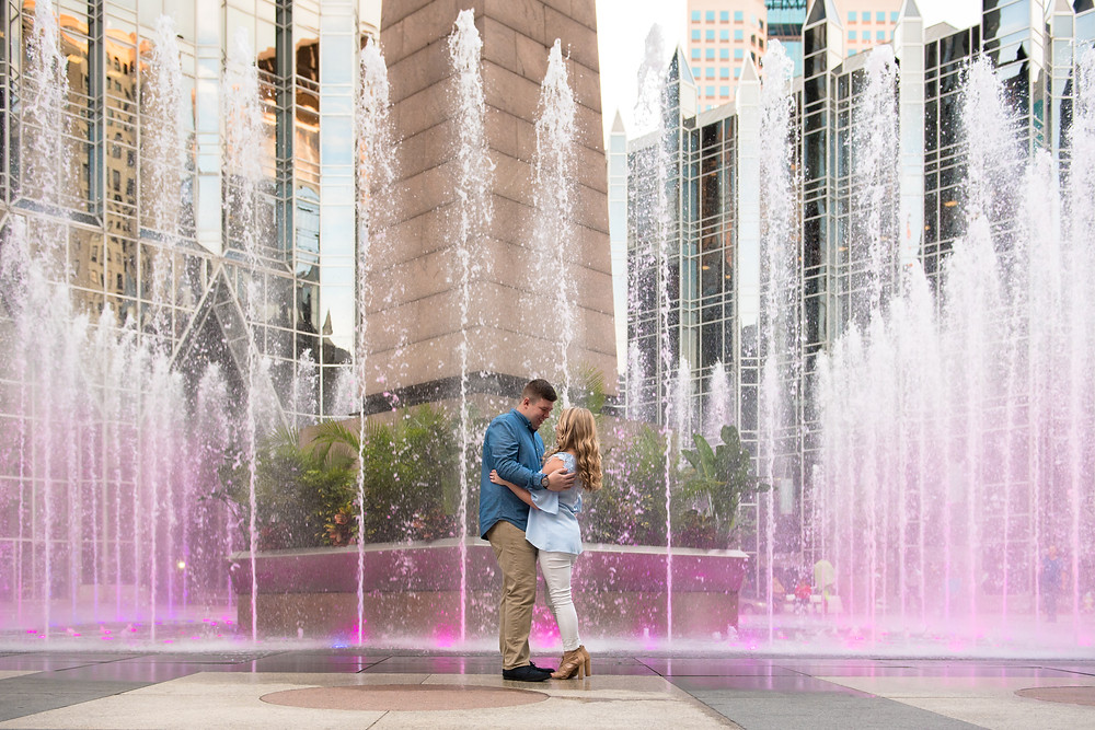 A Pittsburgh engagement with the couple standing together in front of the fountains at PPG Place downtown.