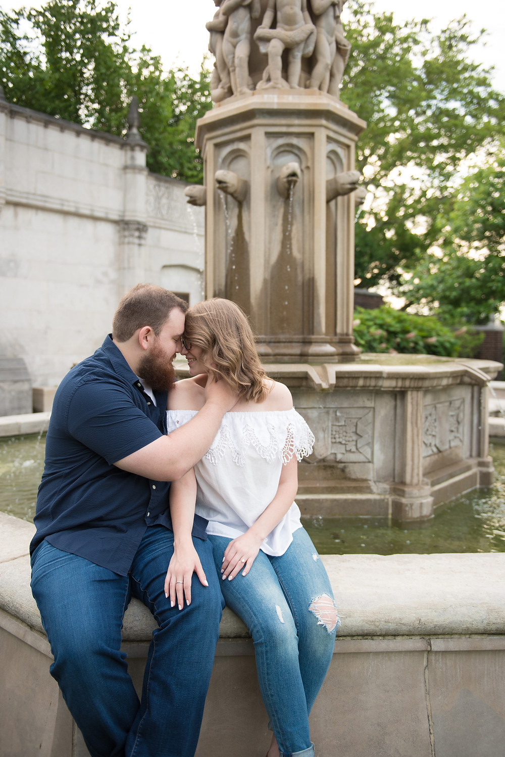 An engagement session in Pittsburgh with the couple posed sitting by the fountain at Mellon Park.