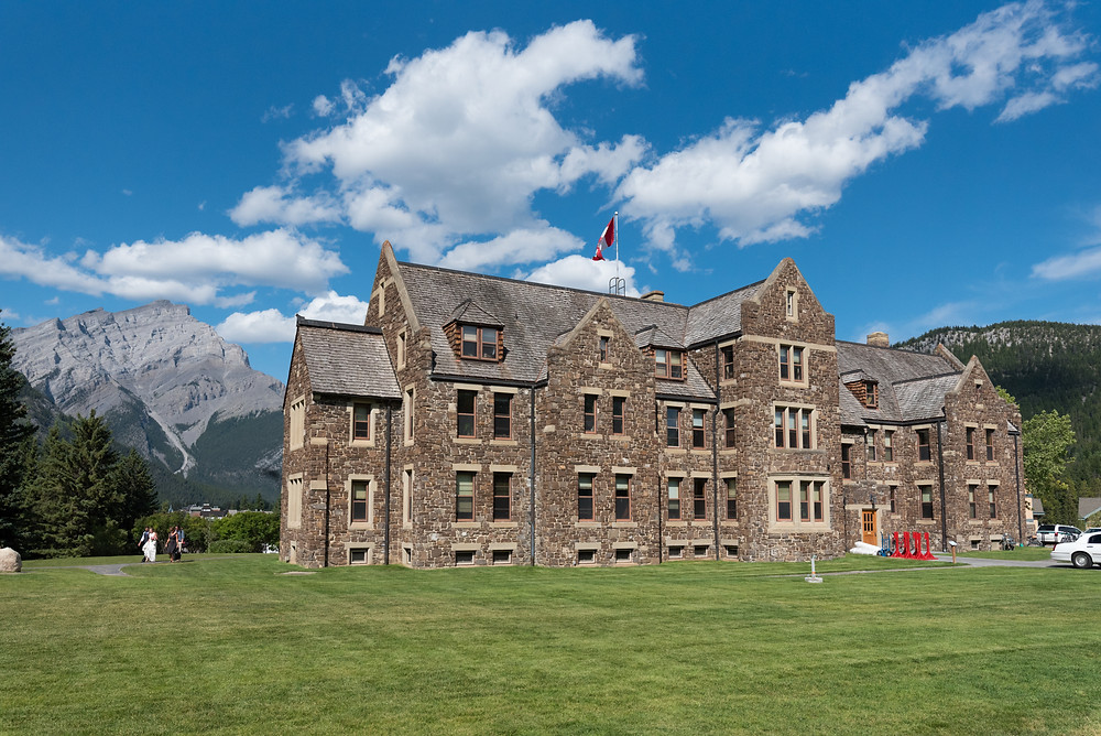 An old stone government building in Banff Canada with mountain peaks in the background