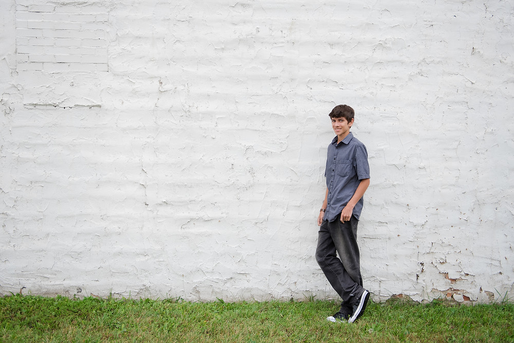 A high school senior boy leaning on a white wall during his senior pictures.