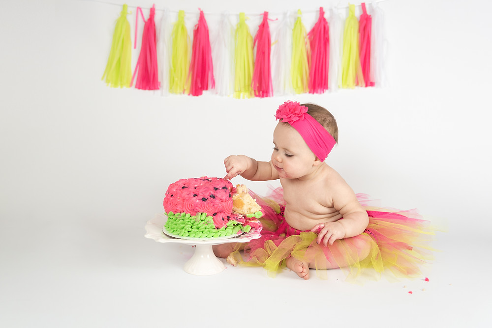 Baby girl in tutu digging into her smash cake. Photo taken on a white background with watermelon themed smash cake.