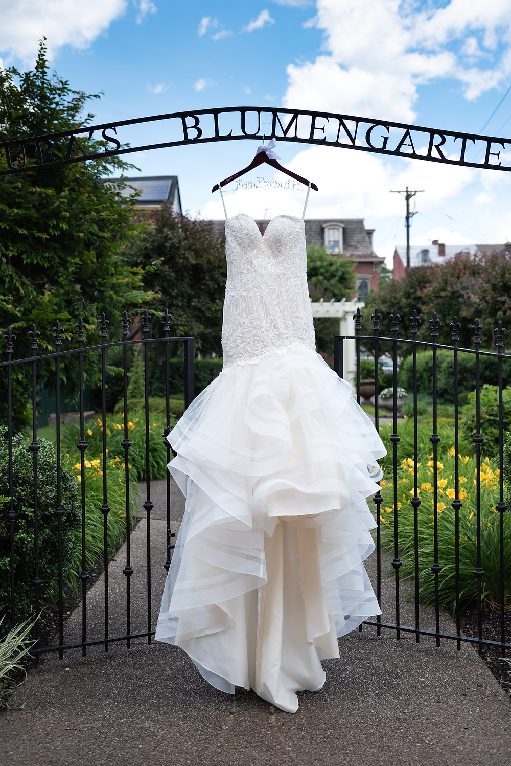 Mermaid style wedding dress hanging in the garden at The Priory in PIttsburgh