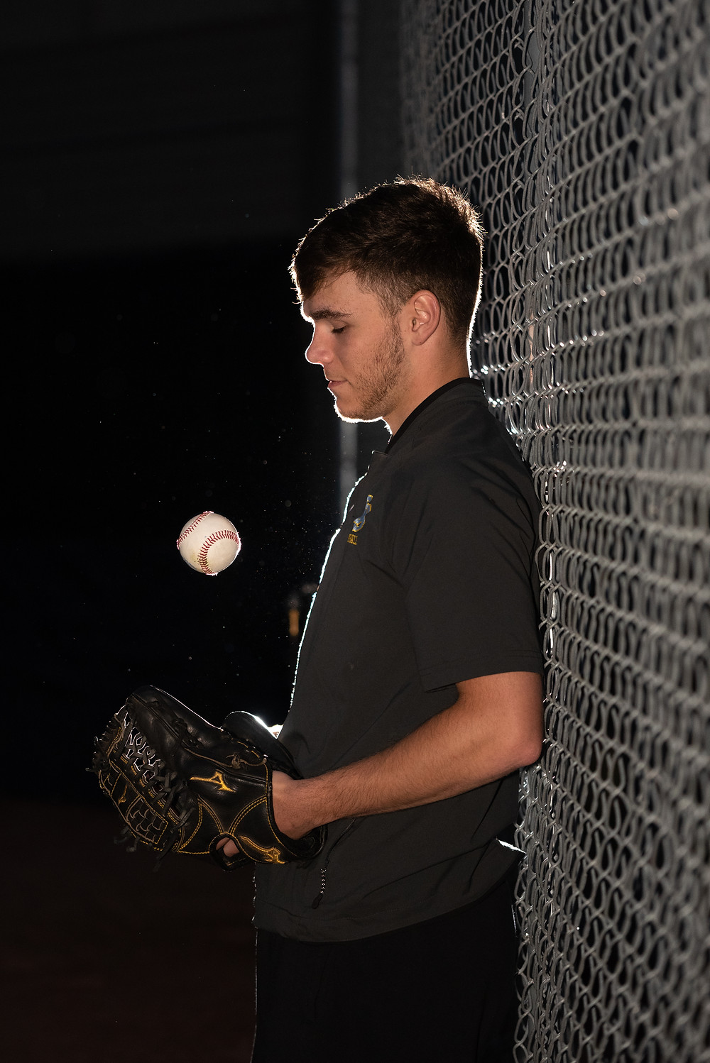 Senior guy tossing baseball at night leaning against a fence with a flash illuminating him