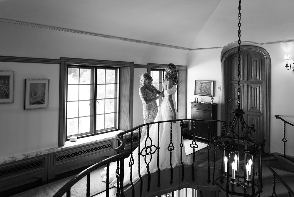 Black and white photo of mother of the bride buttoning the bride's dress at the top of the staircase