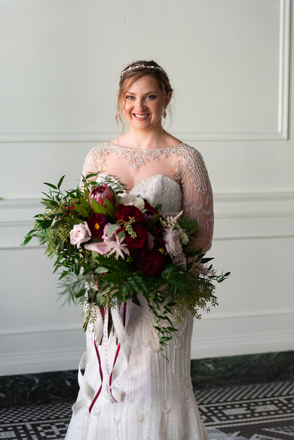 Bride holding burgundy and pink boquet at the George Washington hotel in Pennsylvania; Bride portrait