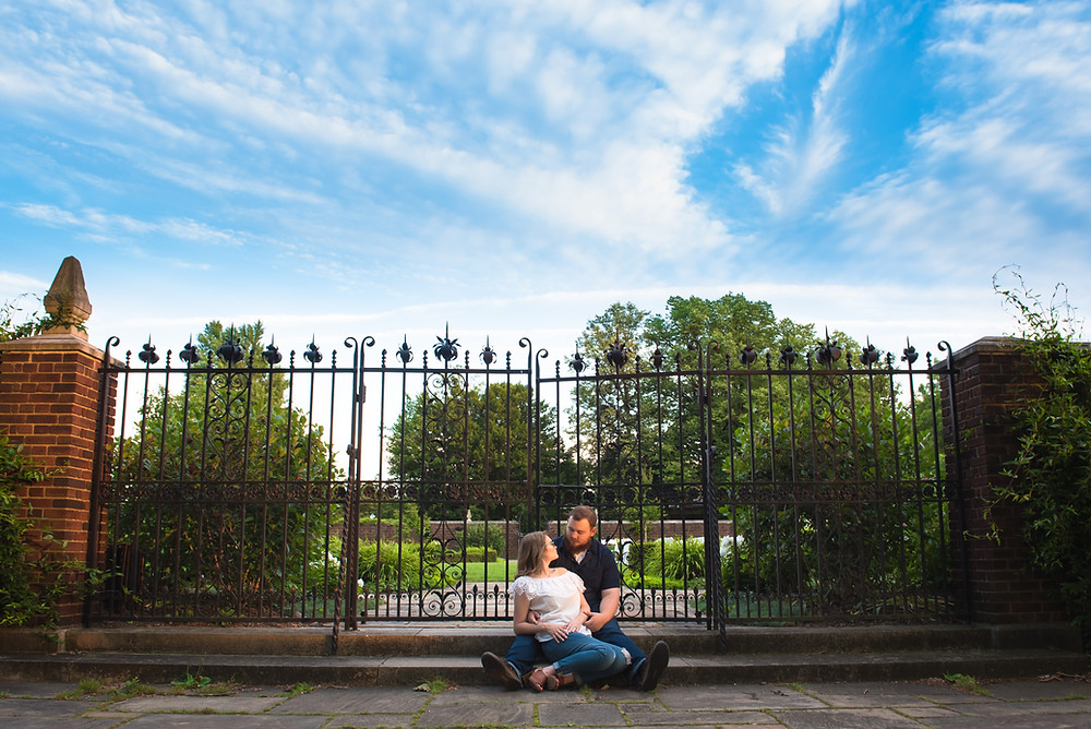A recently engaged couple sitting on stone steps in front of a large iron gate during their photo session in Pittsburgh.