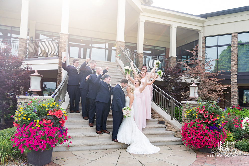 Bridal party celebrating on the stairs of The Lake Club of Ohio.