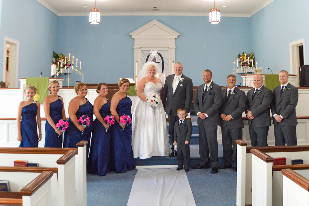 <alt>A picture of the bridal party lined up in the front of the church</alt>