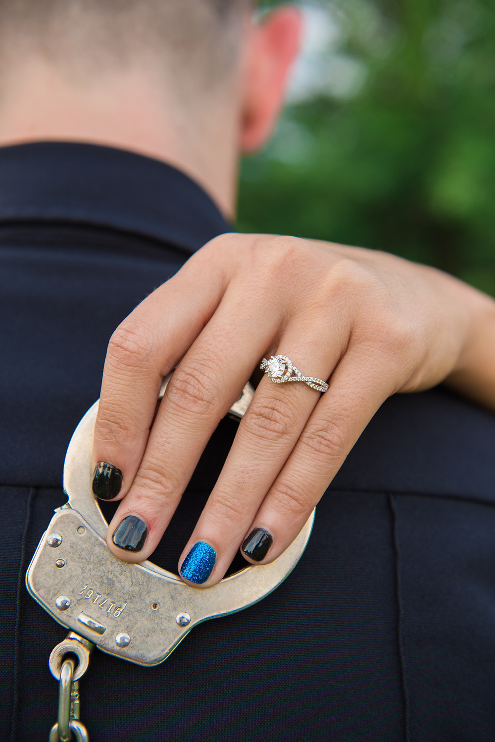 Blue a black police themed fingernail polish with the diamond engagement ring.