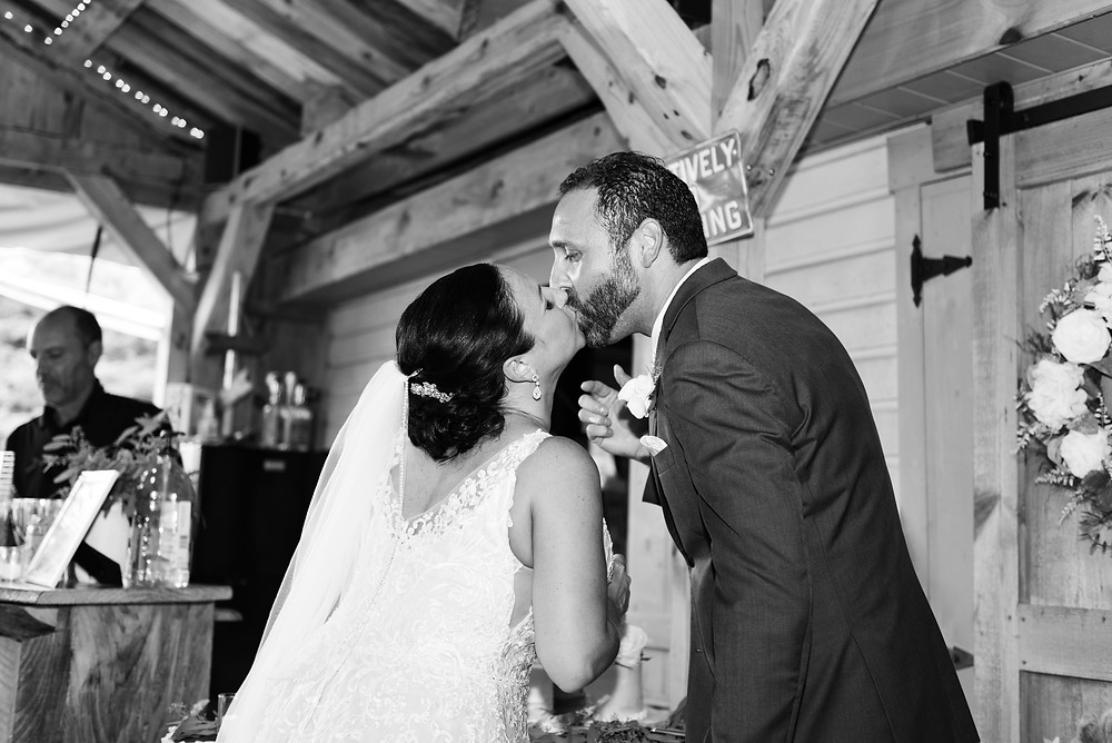 Black and white photo of the bride and groom kissing after cutting the cake at The Dance Hall at Waterman Farms in Jefferson Hills, PA