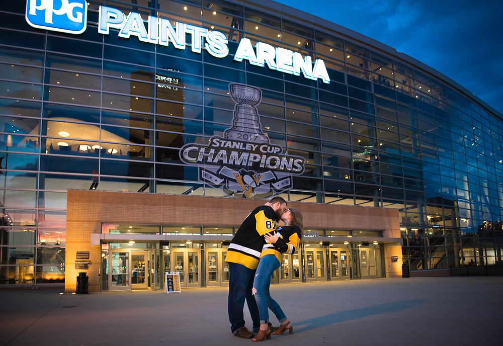 Couple wearing Pittsburgh Penguins jerseys standing in front of PPG Paints Arena in Pittsburgh, Pennsylvania during their engagement shoot.