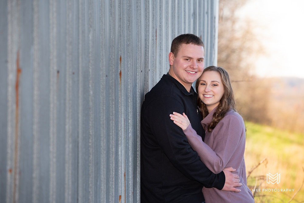 Country engagement session with couple leaning on barn