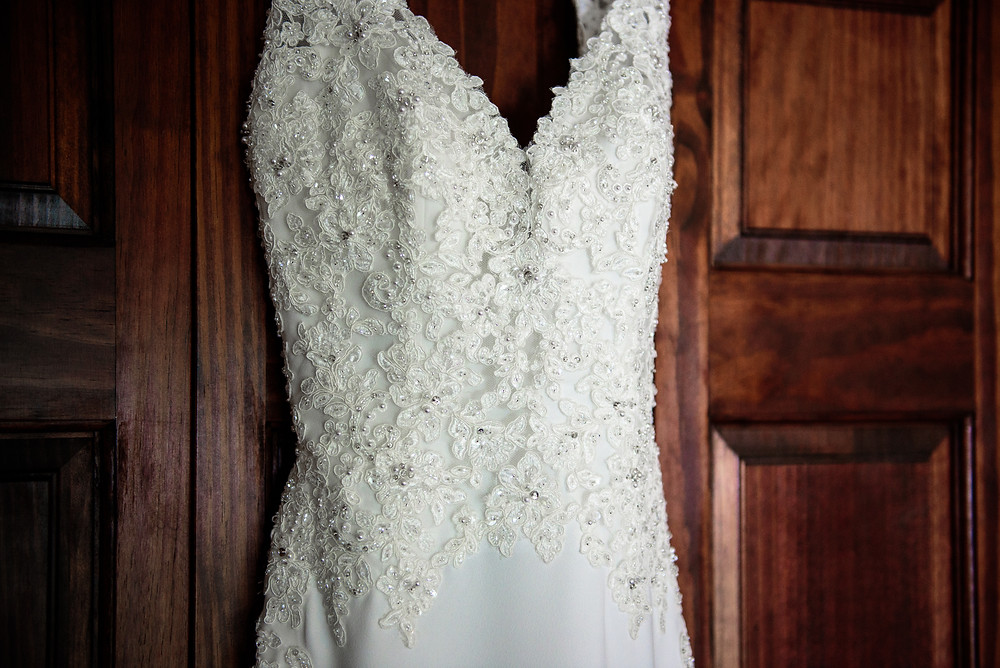 A photograph of the bride's dress hanging on a door before the wedding.