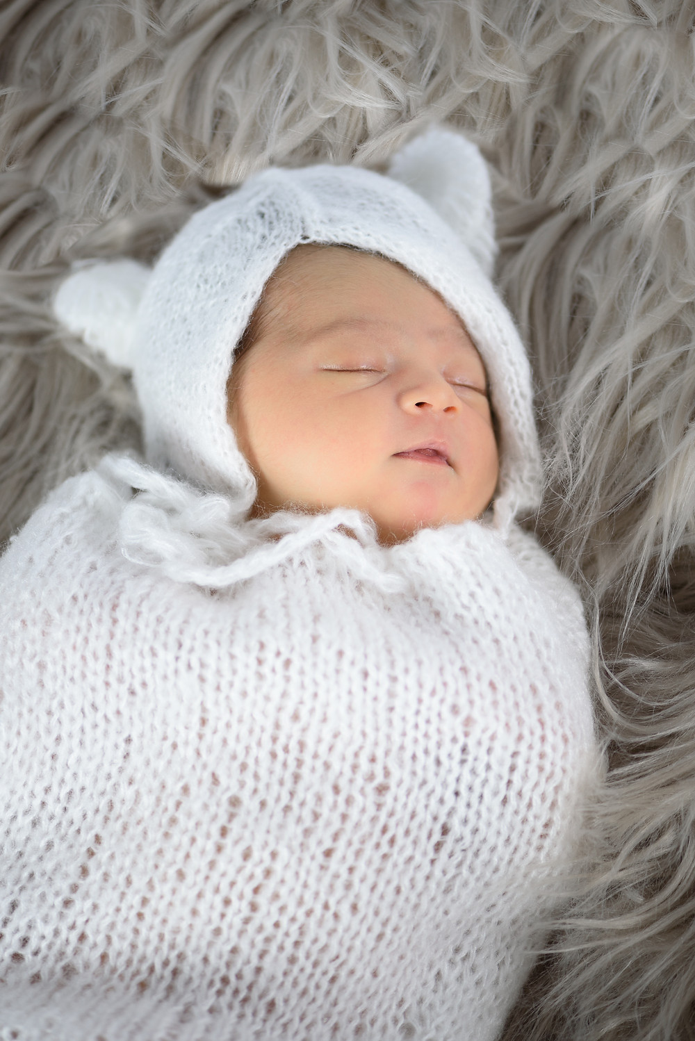 Newborn girl posed on a fur blanket sleeping. She is wearing a knit teddy bear outfit.