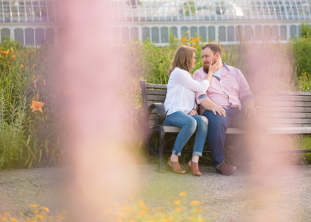 The newly engaged couple sitting on a bench surrounded by bright colored flowers in front of Phipps Conservaotry