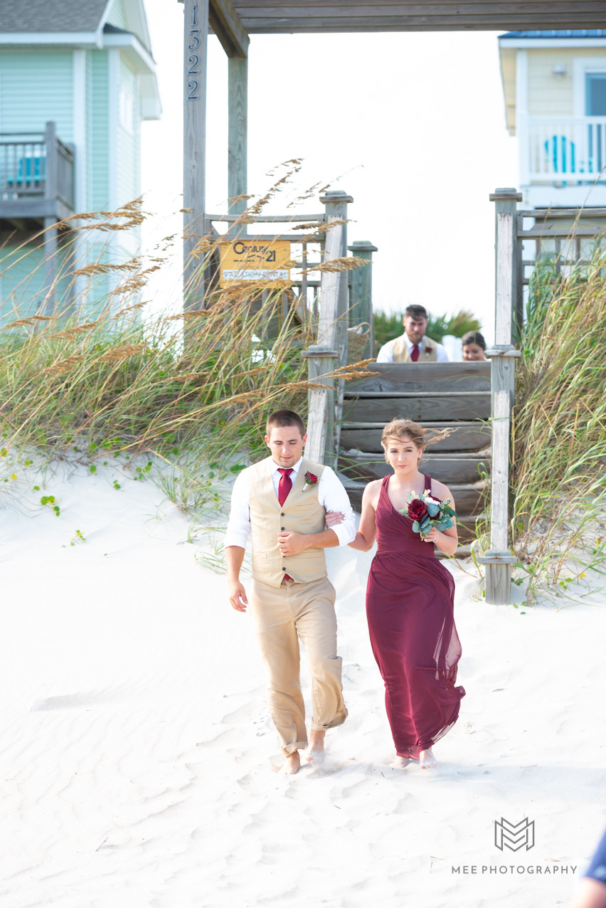Groomsmen and bridesmaids walking down aisle during beach wedding at North Topsail