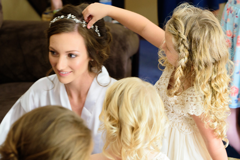 The flower girl playing with the bride's headband.