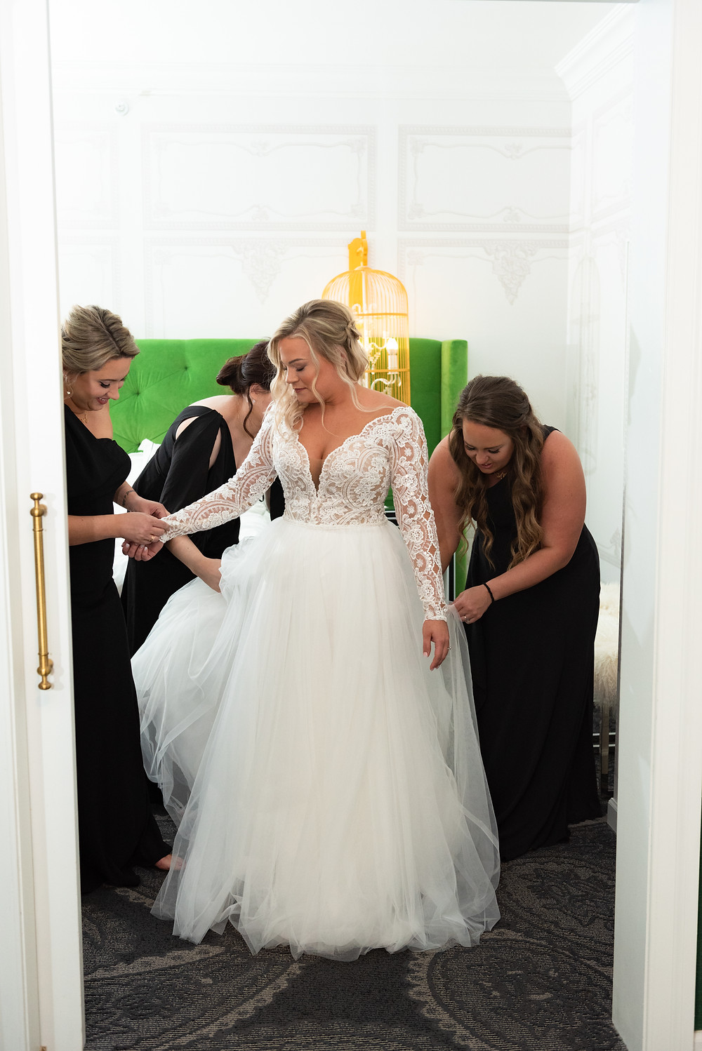Bridesmaids in black dresses helping the bride into her Maggie Sottero gown