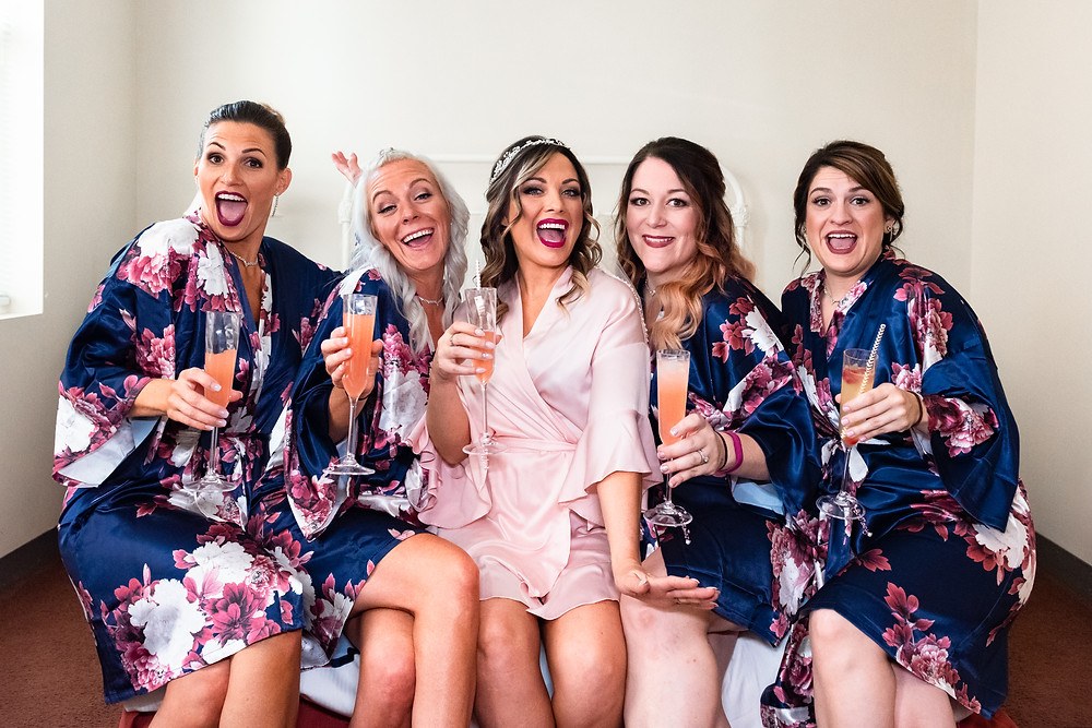 Bride and bridesmaids in matching robes toasting with champagne before the ceremony at the Priory