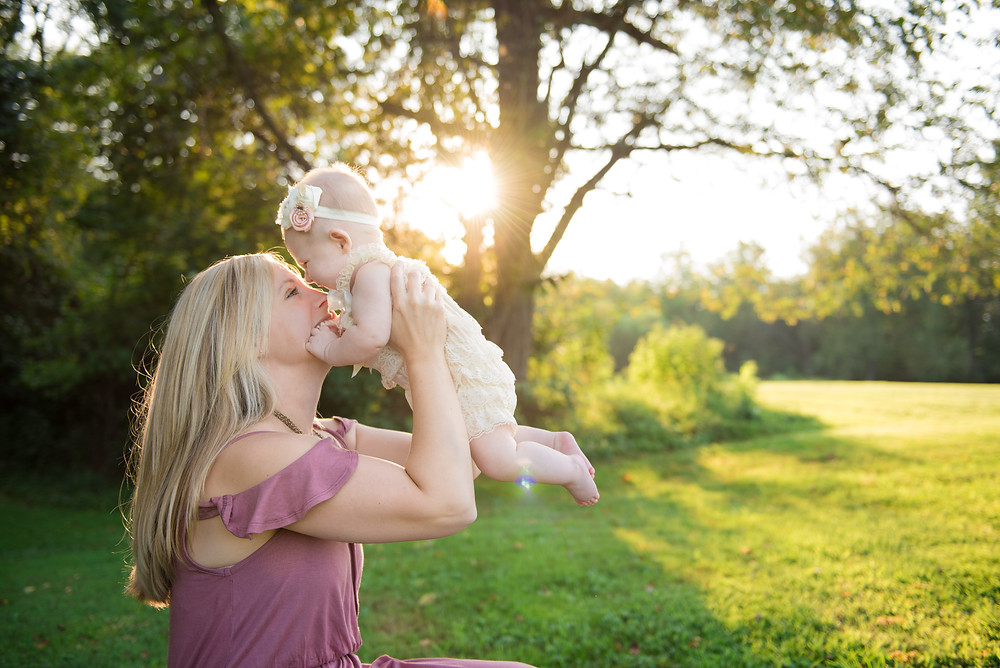 Momma and baby laughing during their photo session near Pittsburgh outside at sunset
