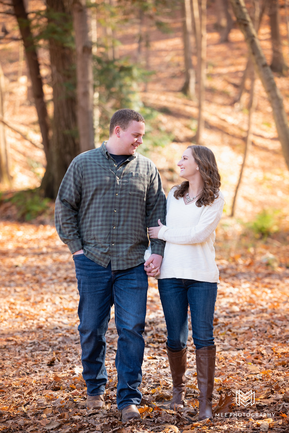Couple walking and laughing during their fall engagement session