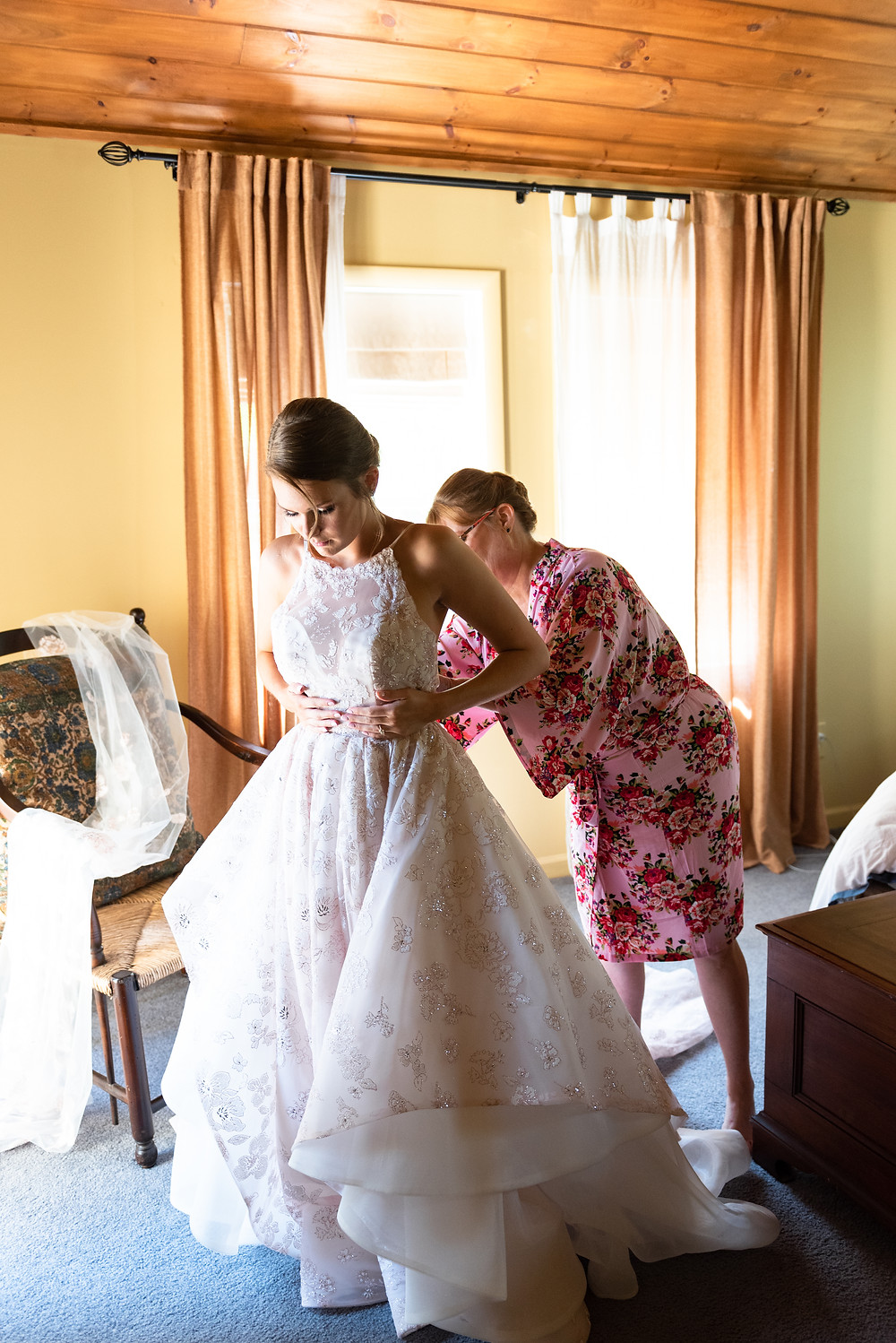 Bride putting on her Hayley Paige dress before the ceremony at Chanteclaire Farm