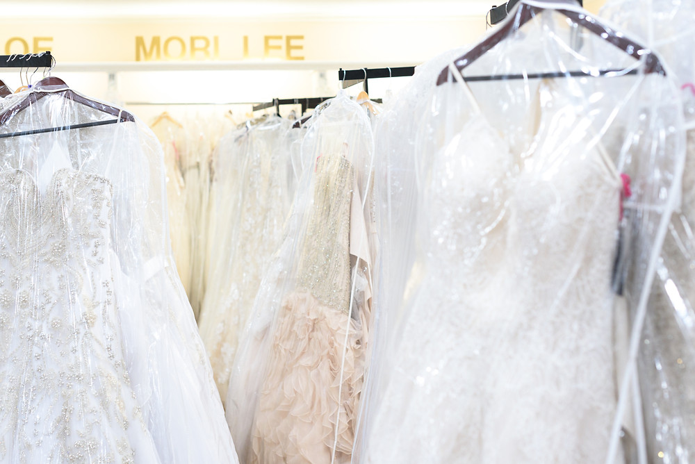 A photograph of Mori Lee designer wedding dresses hangin on the racks at Babette's gowns.