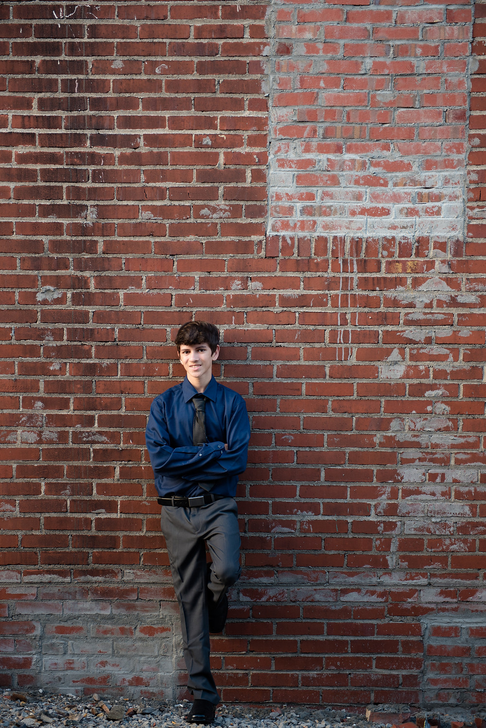 A guy's high school senior pictures in front of a brick wall near Pittsburgh.