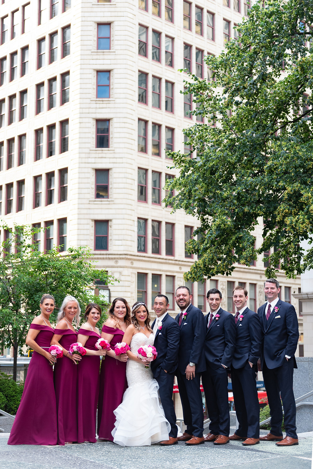 Bridal party portrait with the bridesmaids wearing burgundy dresses in Mellon Square