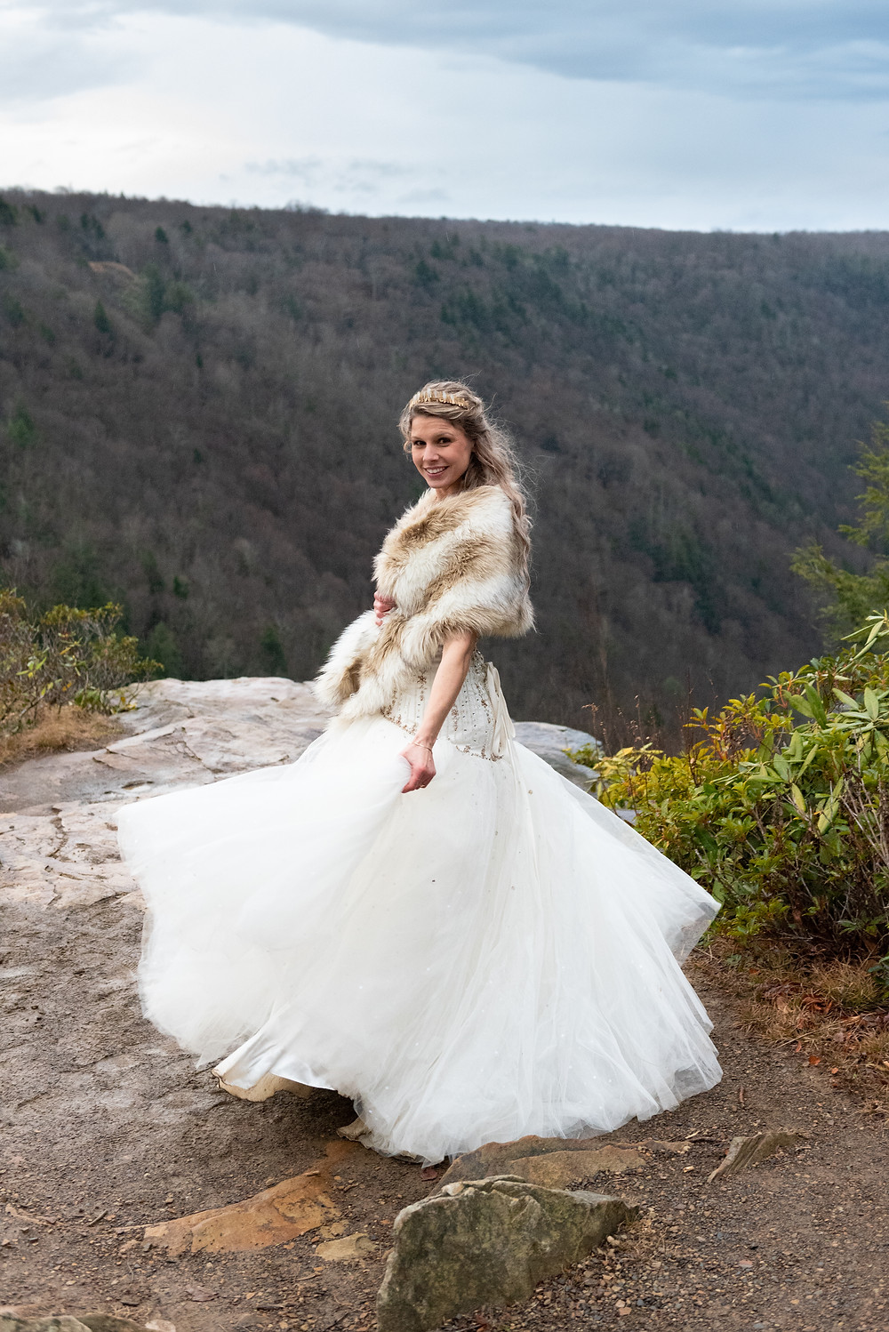 Bride spinning in her dress with the rolling hills of WV in the background