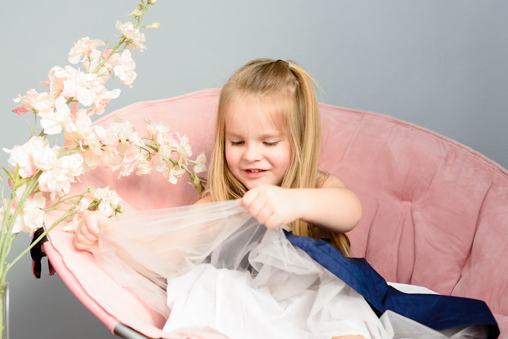 Girls fourth birthday photo shoot. Girl playing with her blue and white dress.