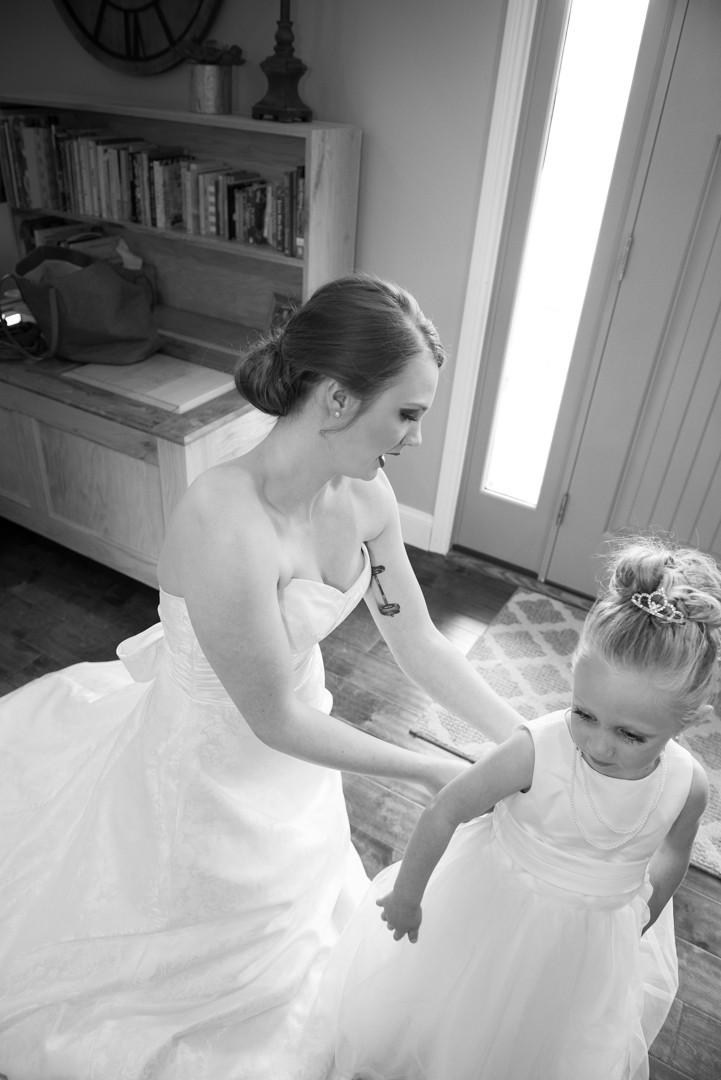 Bride helping flower girl get dressed