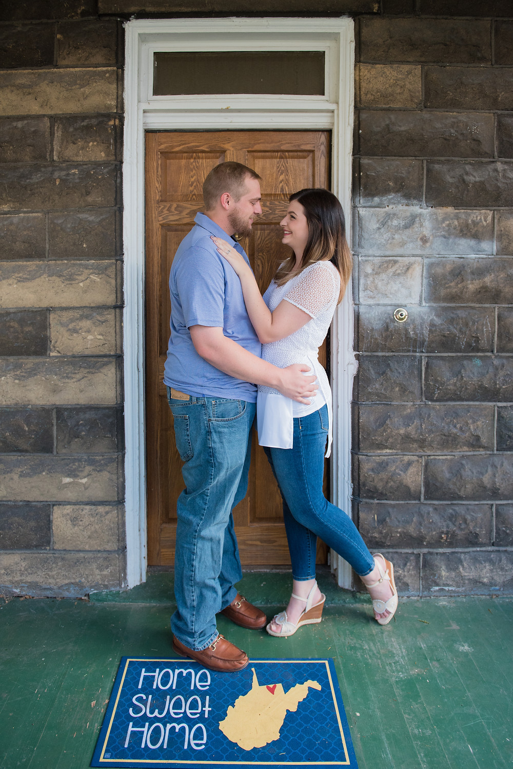 Newly engaged couple posed in front of their door of their new home