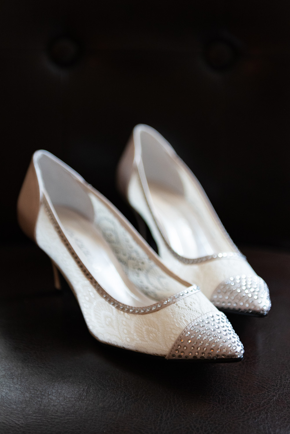 Ivory lace wedding shoes sitting on a black chair at the Priory