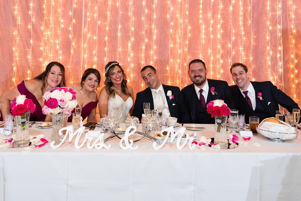 Bridal party sitting at the head table and smiling for a photo