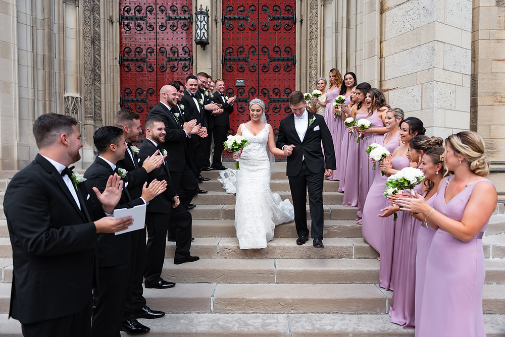 Bride and groom exiting Heinz Chapel with bridesmaids and groomsmen cheering
