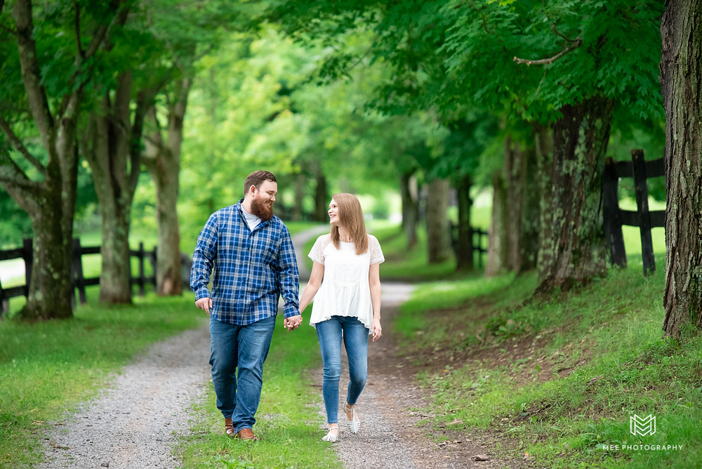 Maryland engagement photos with couple walking and holding hands at Chanteclaire Farm in western Maryland.