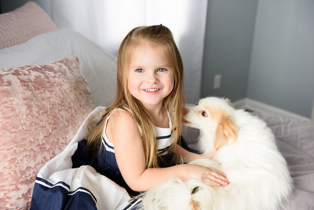 Girl sitting on a pink and gray bed while smiling at the camera. She is playing with a white, fluffy dog.