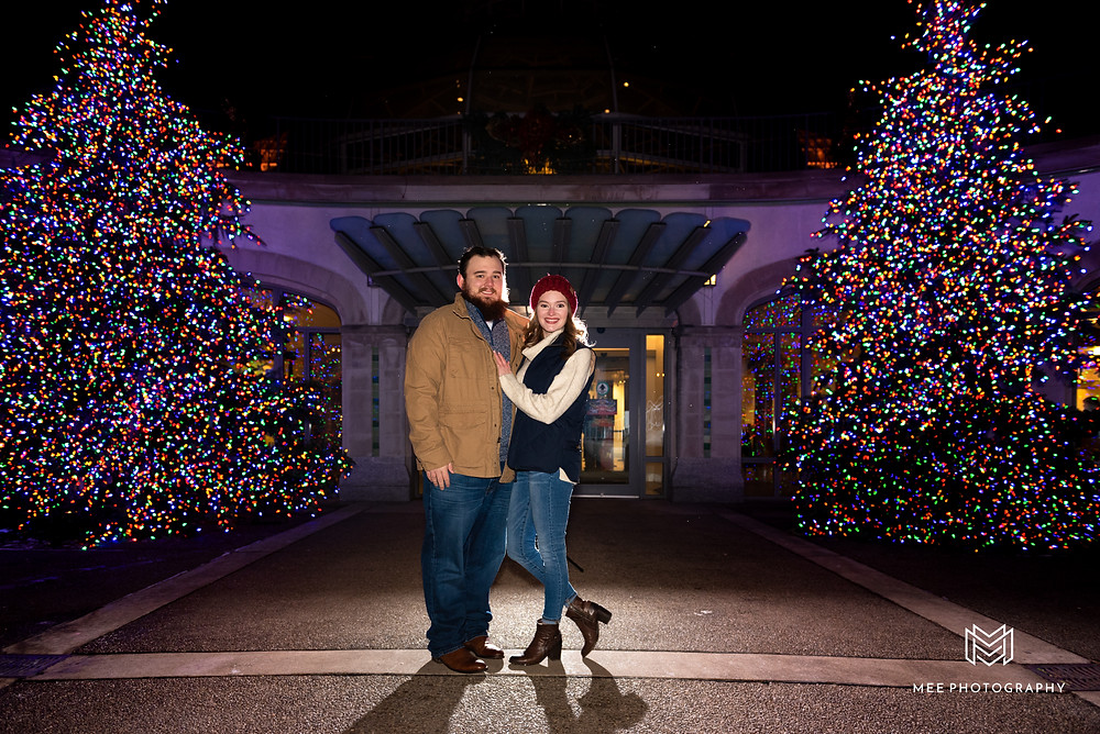 Christmas engagement photos in front of Phipps Conservatory in Pittsburgh at night with lit christmas trees